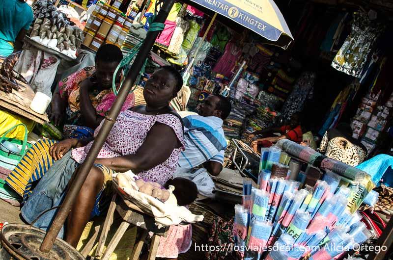 mujer sentada bajo una sombrilla rodeada de mercancías foto inclinada