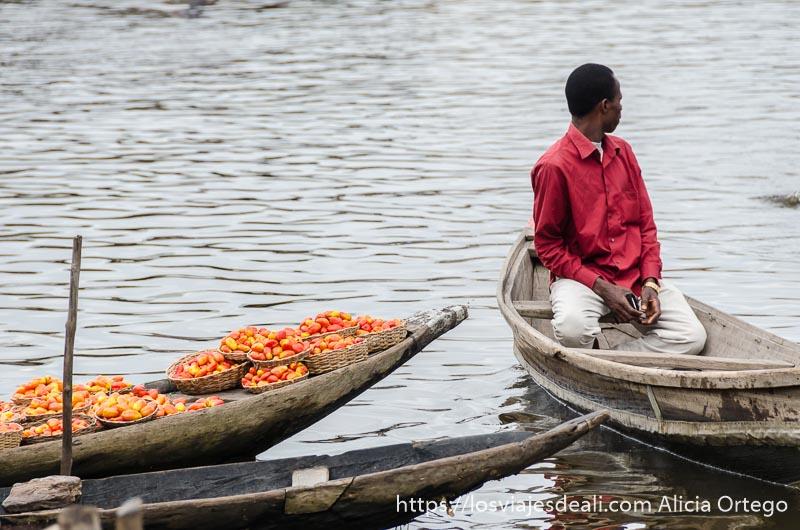hombre en una barca con camisa roja junto a otra llena de tomates rojos en ganvie