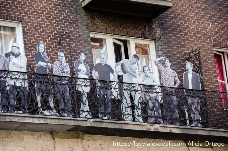 figuras de cartón de fotos de gente asomada a un balcón a tamaño real pero en blanco y negro calles de budapest