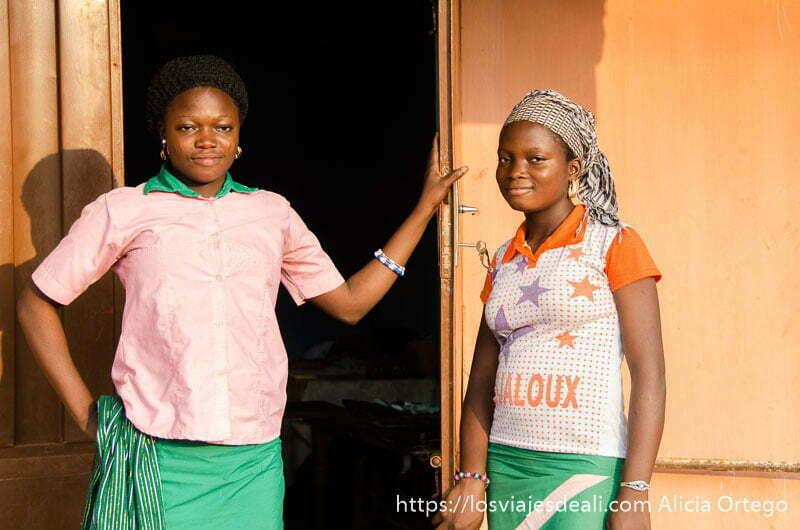 dos chicas peluqueras con uniforme en la puerta de su negocio al atardecer en abomey benin