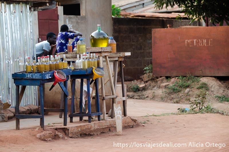 puesto de gasolina junto a la carretera es una mesa de madera con grandes botellas llenas de gasolina y aceite en abomey