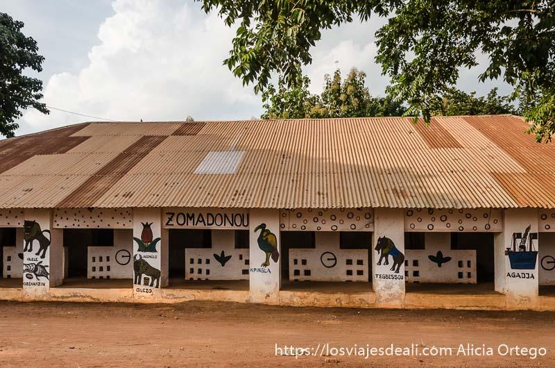 palacio de abomey de un solo piso con tejado de chapa y columnas con animales pintados patrimonio de la humanidad de benin