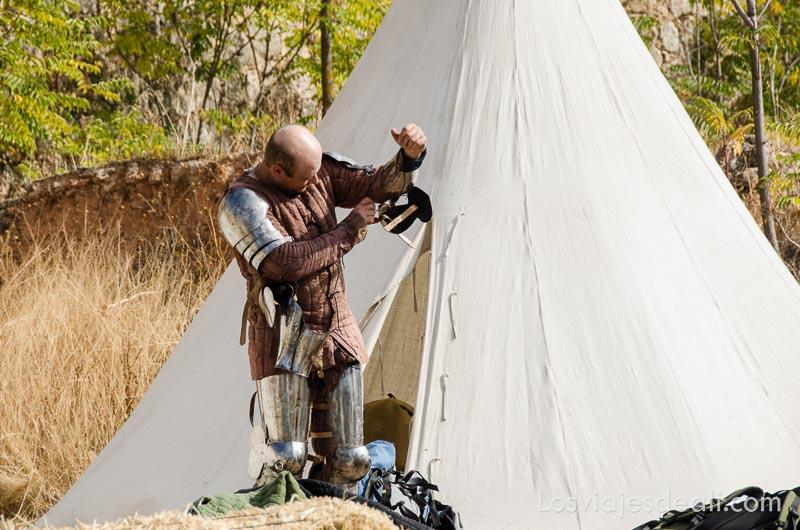guerrero colocándose armadura en la puerta de su tienda torneo internacional de combate medieval