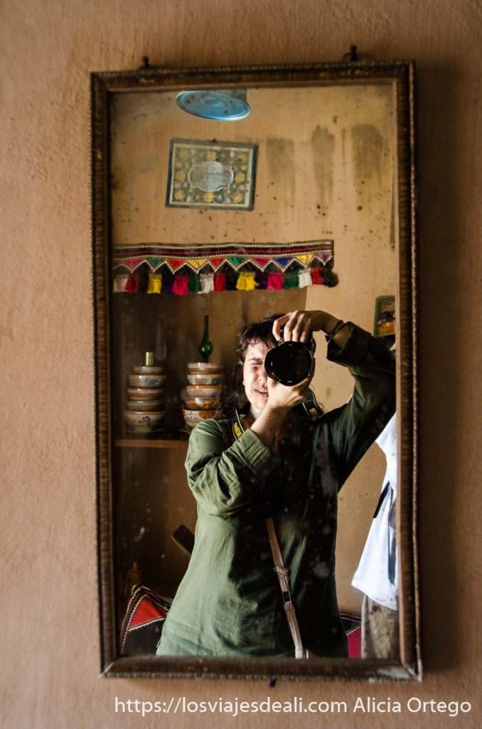 haciéndome una foto aprovechando un espejo antiguo en una pared de adobe visitas que hacer cerca de salalah