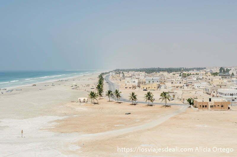 pueblo de tahaq junto a la playa con hilera de palmeras y casas bajas de color blanco o beige visitas que hacer cerca de salalah