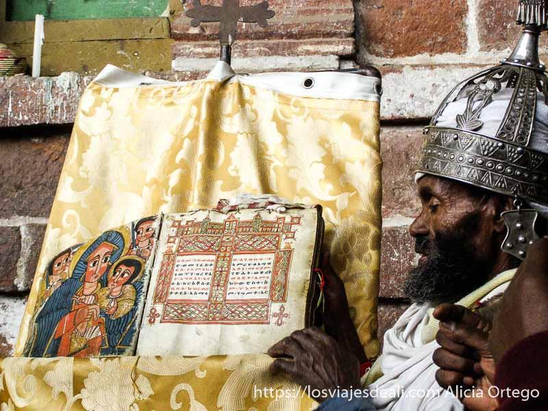 cura etíope mostrando antigua biblia con dibujos iglesias de etiopía