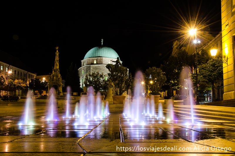 foto nocturna fuente con chorros que salen del suelo y mezquita al fondo qué ver en pécs