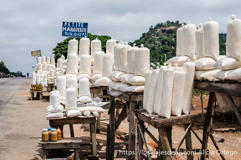 venta de harina en bolsas cilíndricas en la carretera y con cartel de vendedora llamada Petit Marguerite ruta en benin