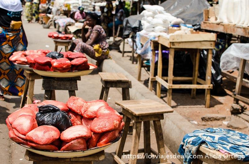 venta de quesos de color rojo en puestos de madera en la carretera ruta en benin