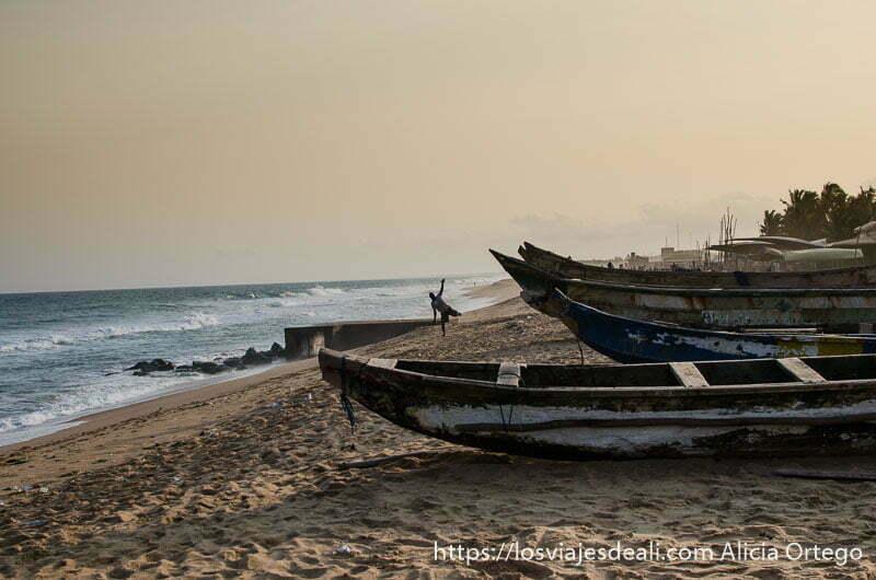 barcas en la playa y un hombre haciendo equilibrios junto al mar en la capital de togo
