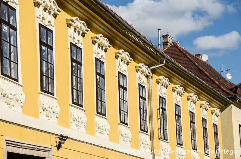 hilera de ventanas en fachada pintada de amarillo en la colina del castillo de budapest
