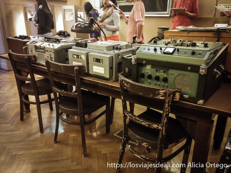 aparatos de radio y escucha antiguos todos juntos una mesa con sillas en la casa del terror de budapest