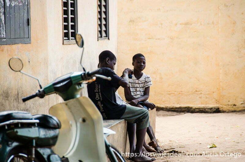 dos niños sentados en un banco con una motocicleta al lado en ouidah benin