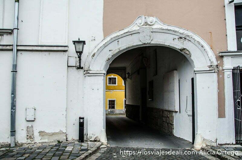 pasaje con arco que atraviesa edificio y al fondo una fachada amarilla en szentendre