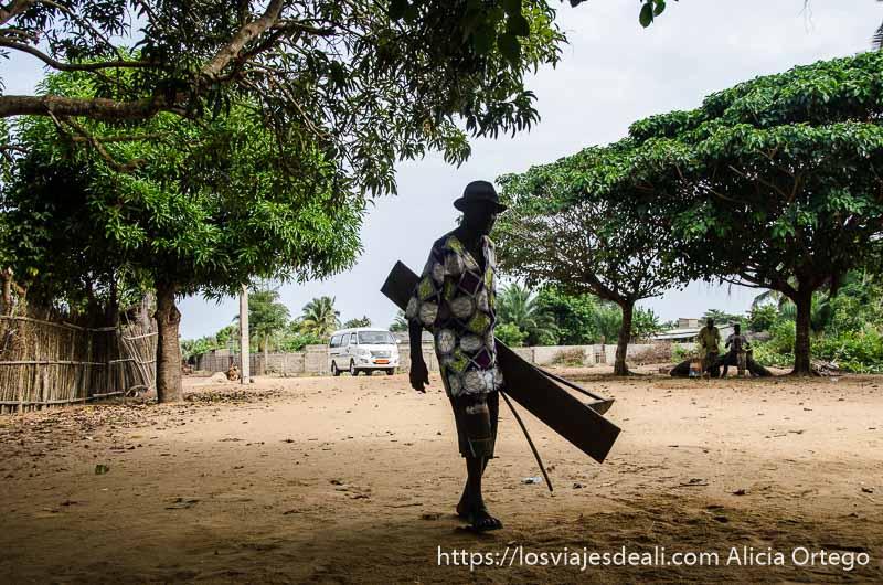 un hombre mayor con sombrero y bastón carga con un tablón ceremonia vudú benin
