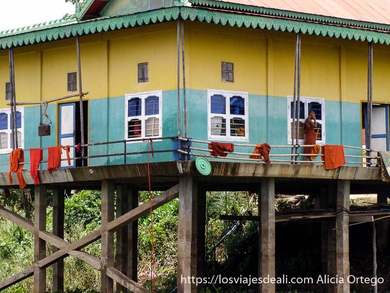 casa de monjes sobre el agua pintada de amarillo y verde excursión cerca de los templos de angkor