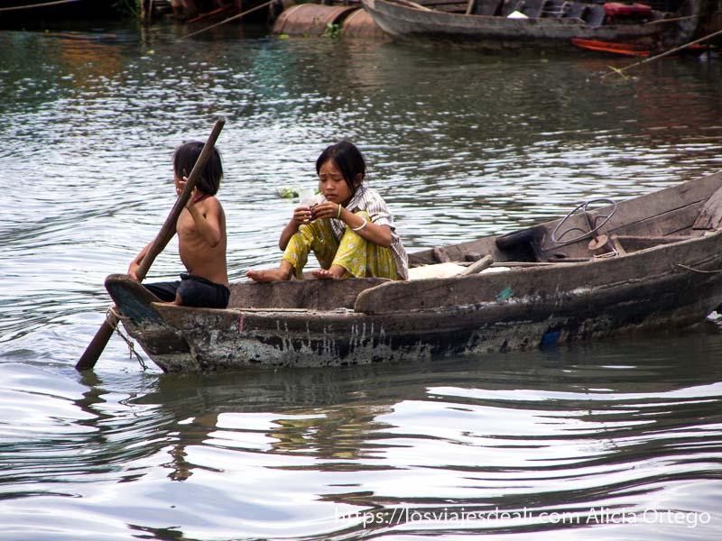 dos niños en una barca excursión cerca de los templos de angkor