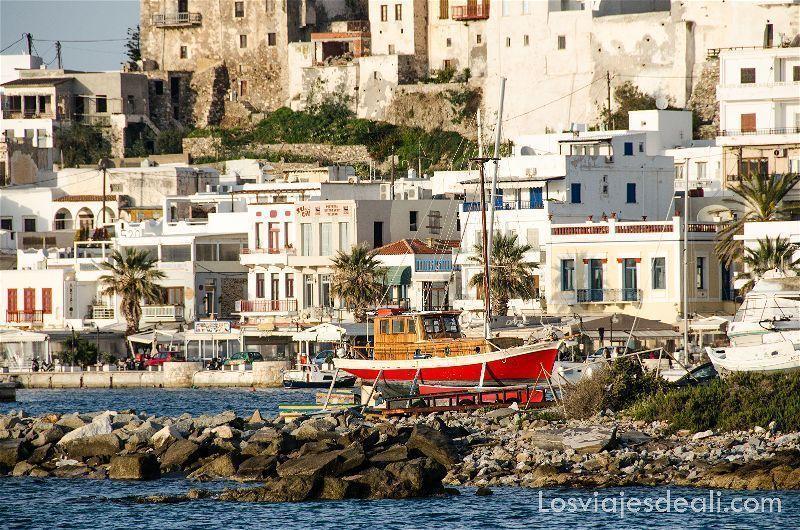 Barco pesquero de color rojo en dique seco con casas de la capital de naxos detrás, con luz de atardecer