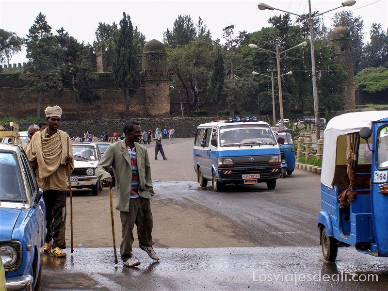 plaza principal de Gondar llena de taxis y rickshaws blancos y azules. Un señor con discapacidad en una pierna cruza y al fondo se ve el castillo