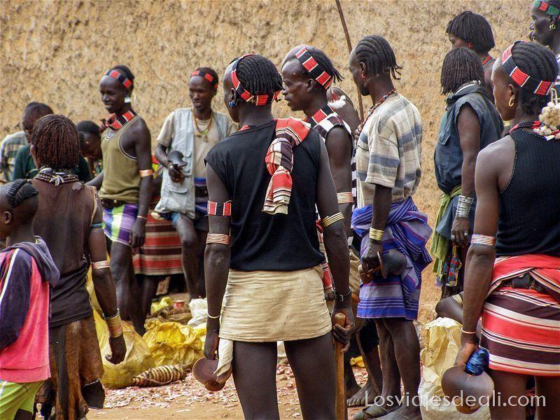 grupo de jóvenes etíopes con peinados de trenzas y diademas y brazaletes hechos con cuentas de colores en uno de los mercados del sur etíope