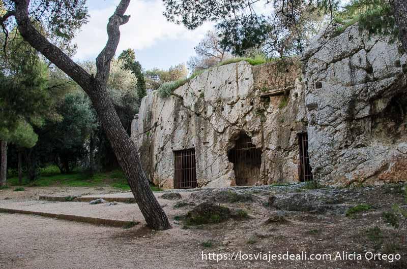 cueva que dicen fue la prisión de sócrates en una colina entre árboles cerca de la acrópolis de atenas y su museo