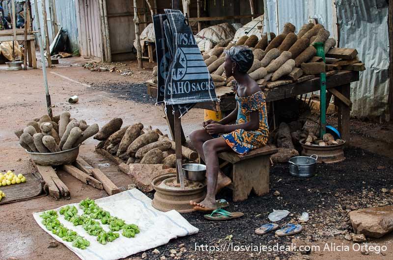 niña sentada en su puesto de ñames y fruta en ruta por el interior de Togo