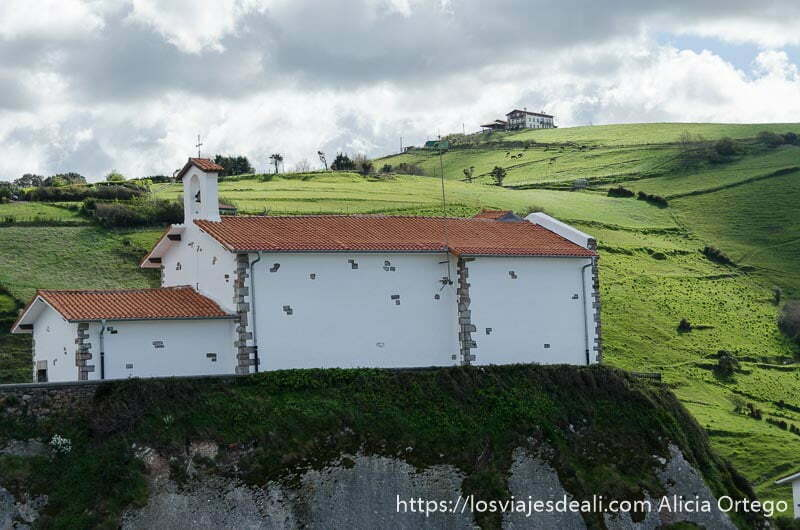 ermita de san telmo pintada de blanco con tejado rojo y pequeño campanario detrás monte verde en zumaia