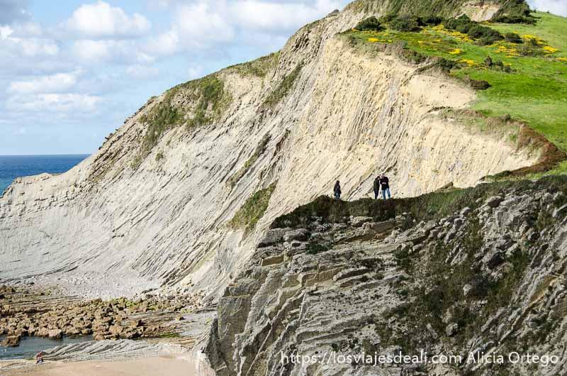 tres personas haciéndose fotos al borde de los acantilados de zumaia