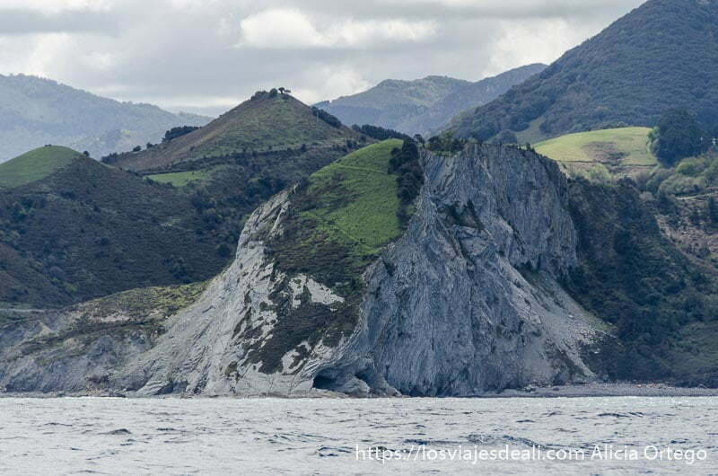 acantilados de flysch desde el mar con montes verdes en parte superior