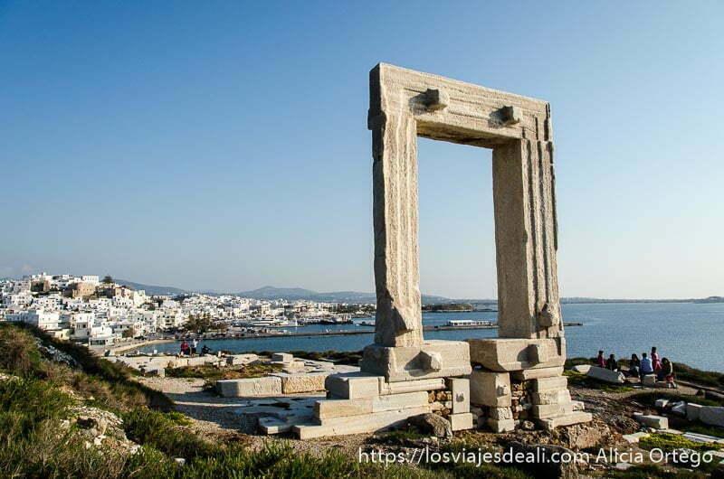 vista de la portara de mármol del templo de apolo con la capital de naxos detrás al fondo