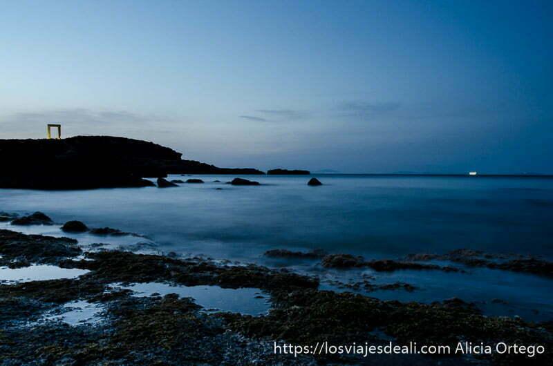 vista de la portara en su islote con playa de piedra delante y mar que parece humo