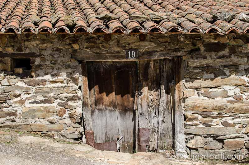 puerta de madera en muro de piedra en la ruta de senderismo fácil en la sierra del rincón