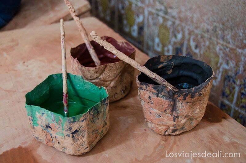 tres recipientes con pintura de colores azul, rojo y verde para cerámica fin de semana de actividades