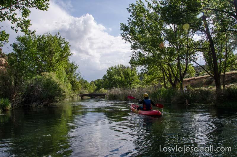 chico en canoa de kayak en río con árboles en las orillas fin de semana de actividades