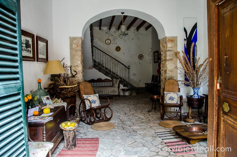 entrada a una casa con mecedoras y arco que da paso al interior en fornalutx