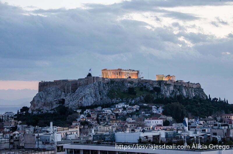 vistas de la acrópolis iluminada bajo cielo nublado y con ciudad a sus pies lugares de interés en atenas