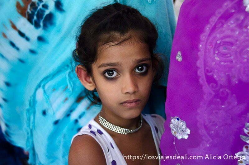 niña india con grandes ojos negros pintados de khol pegada al sari violeta de su madre qué ver en delhi
