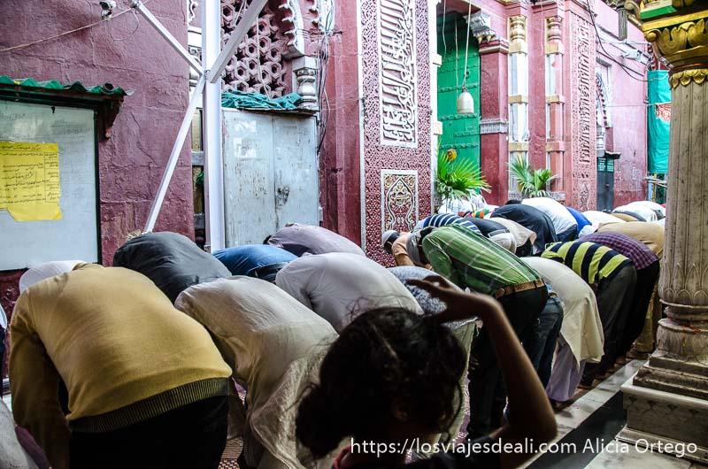 hombres musulmanes agachados en dos filas rezando qué ver en delhi