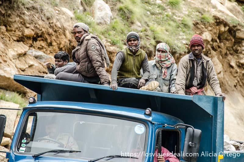 grupo de hombres subidos al techo de un camión azul carreteras del himalaya indio
