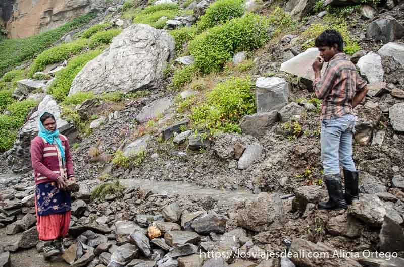 una mujer carga con una piedra en el borde de una de las carreteras del himalaya indio