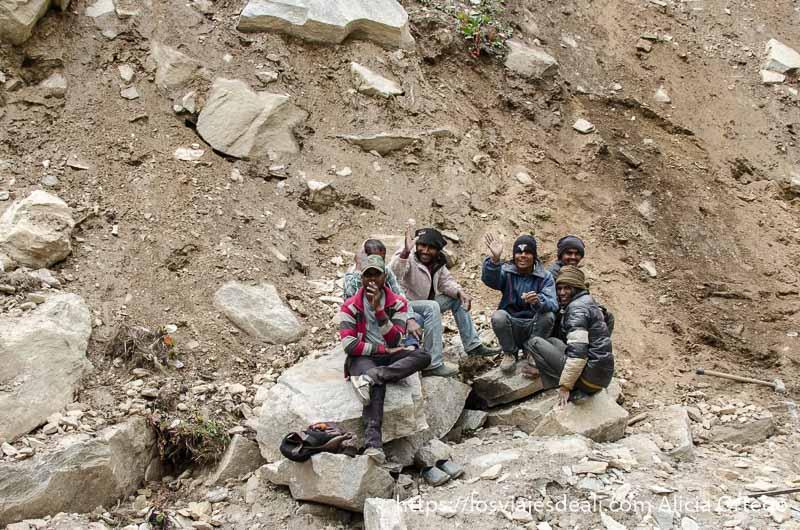 6 hombres sentados en una piedra saludan a los coches con grandes sonrisas carreteras del himalaya indio