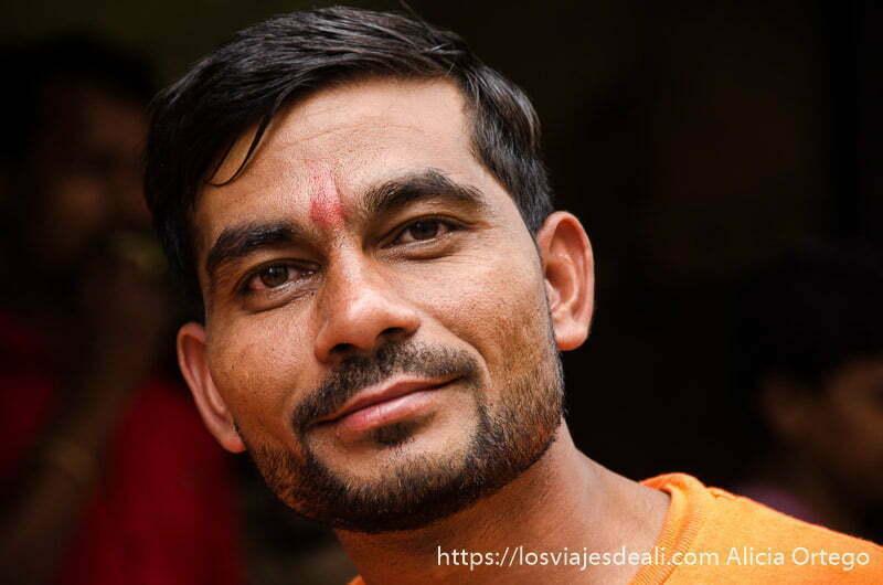 hombre guapo con camiseta naranja y tikka roja en la frente en haridwar