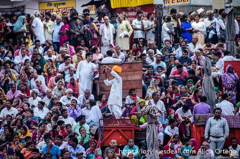 multitud sentada en las gradas y un hombre con turbante naranja fosforito en el centro en haridwar