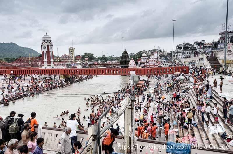 panorámica de ghats con puente que cruza el río todo lleno de gente en haridwar