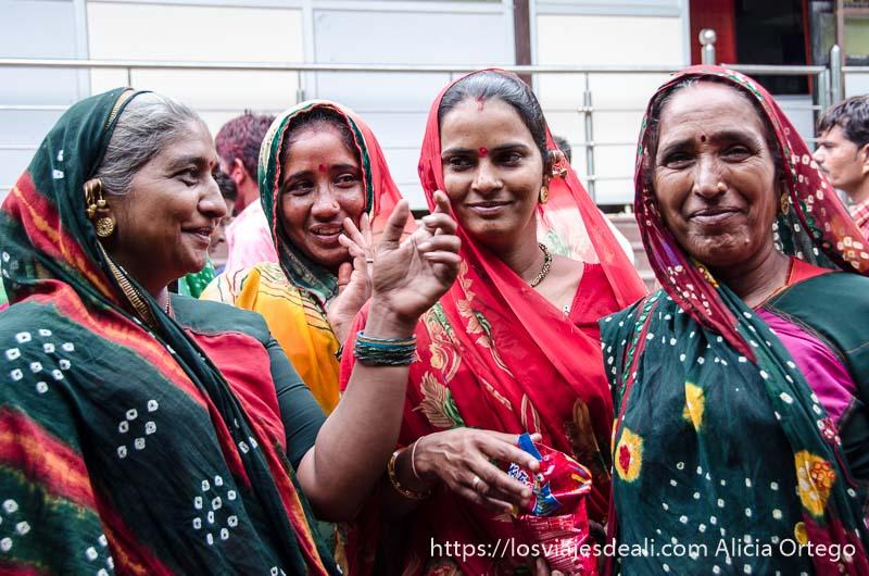 mujeres de rajastán con saris verdes y rojos y pendientes de oro en haridwar
