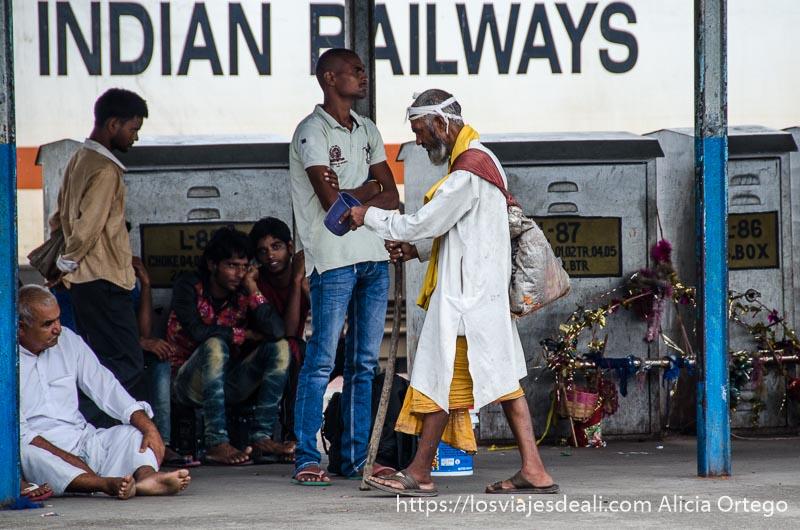 mendigo con muleta en estación de tren para ir a haridwar