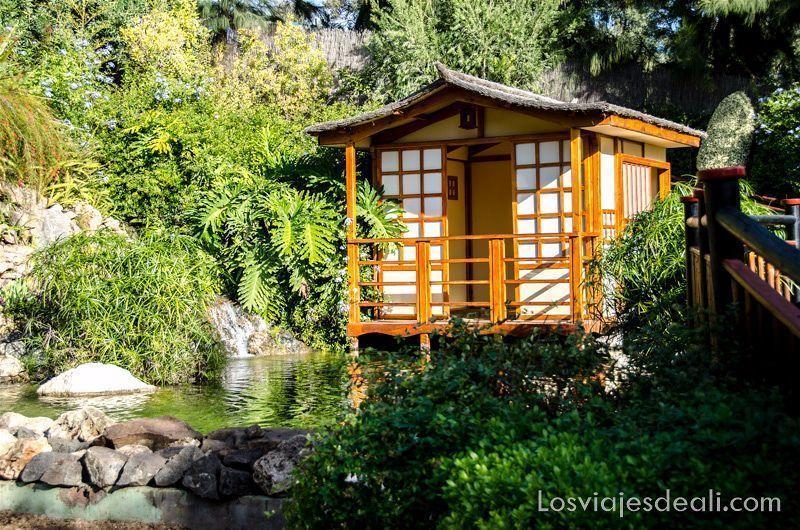 casita japonesa con un lago delante y plantas de bambú junto a un puente japonés en el Molino de Inca