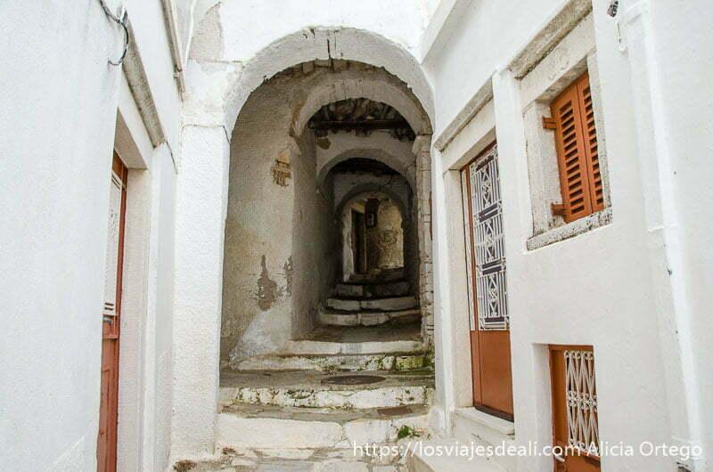 calle con arco de casas blancas con puertas de color teja pueblos del interior de naxos
