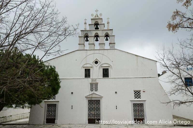 iglesia blanca con campanario de 4 campanas bajo cielo nublado pueblos del interior de naxos
