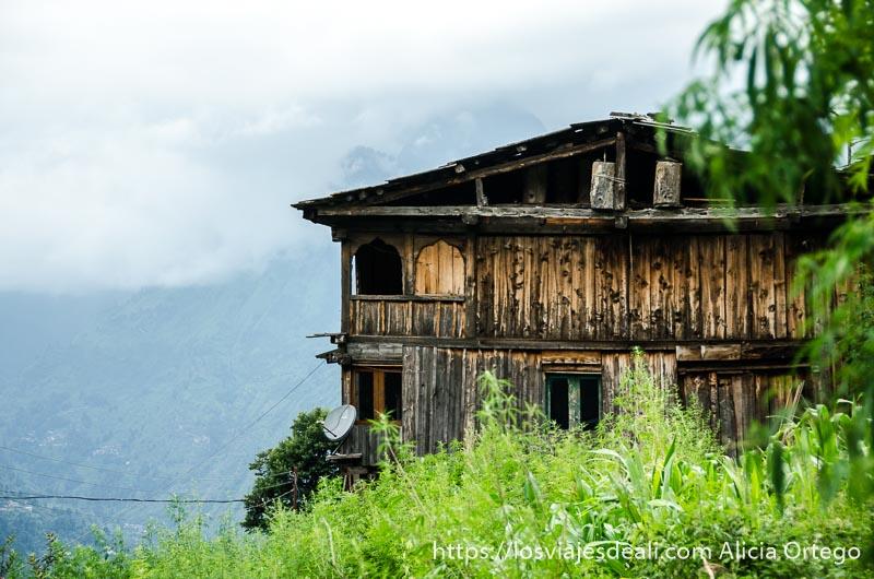 casa de madera de dos pisos y tejado inclinado con montañas y cielo nublado detrás que ver en manali